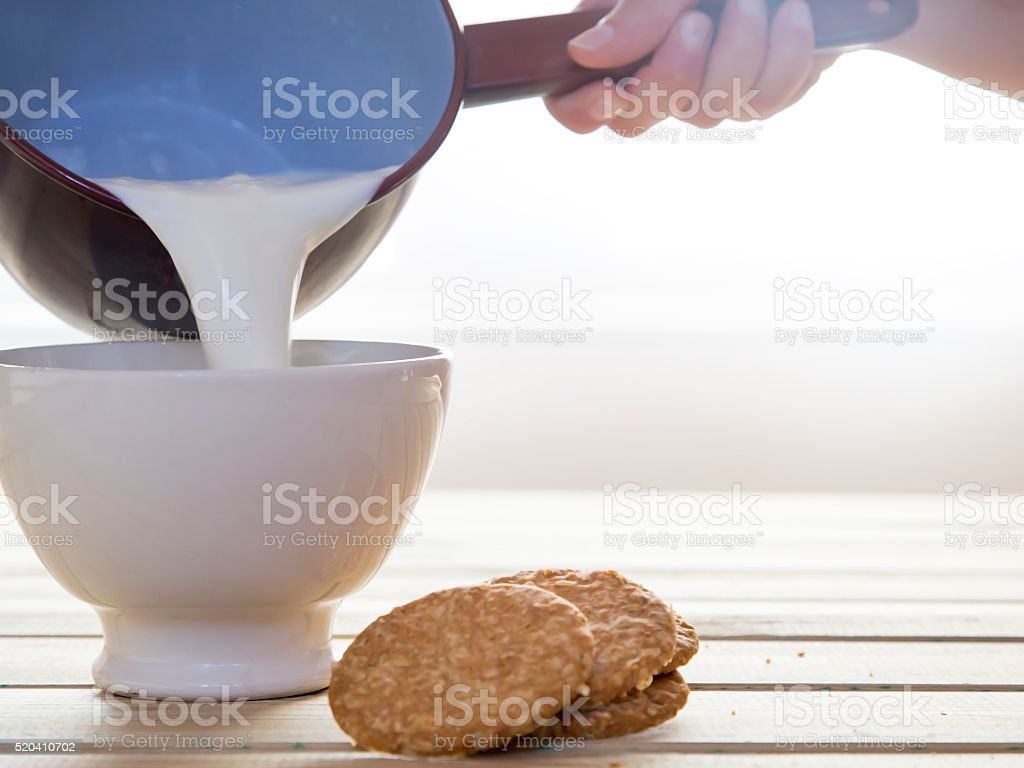 Woman hand holding a saucepan that pour milk in bowl stock photo