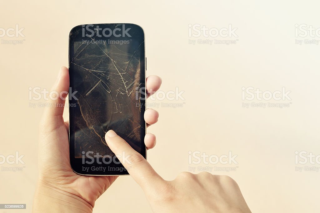 Woman hand holding a smartphone with cracked screen stock photo