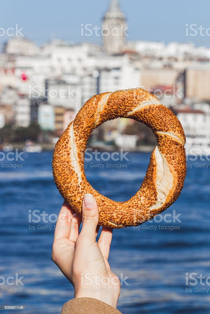 Woman hand holding a traditional Turkish simit on sea background stock photo