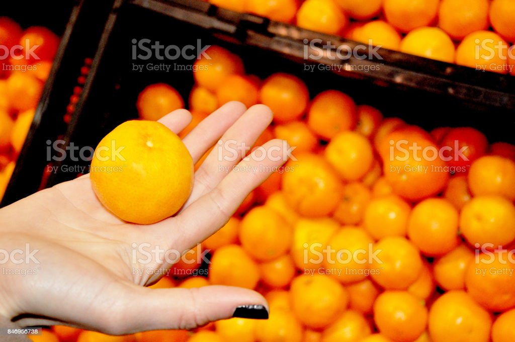Woman hand holding an orange in a greengrocery stock photo
