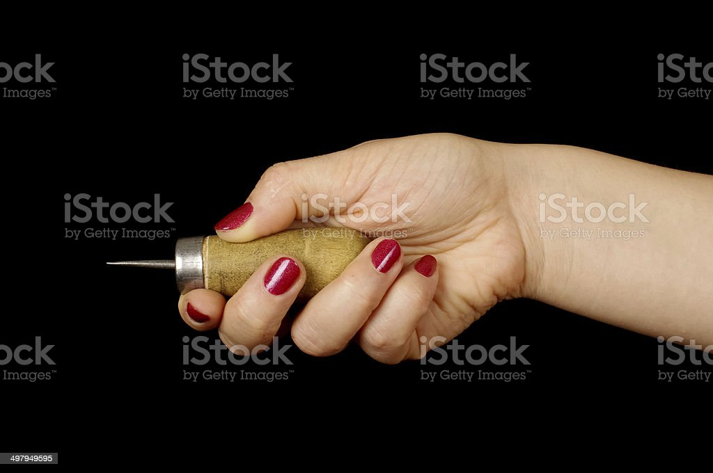 Woman hand holding awl isolated on the black stock photo