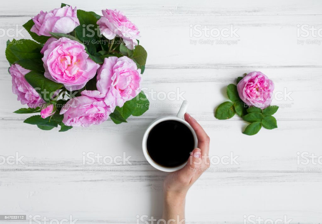 Woman hand holding cup of coffee, surrounded with rose flowers against white vintage wooden table. Flat lay, top view stock photo