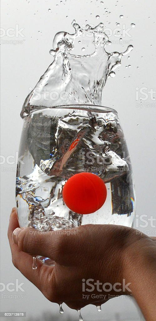 Woman hand holding glass with red ball splashing water stock photo