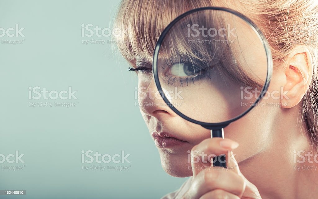 Woman hand holding magnifying glass on eye stock photo