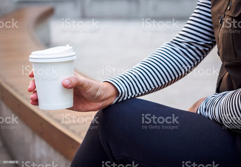Woman Hand holding Paper Cup coffee in Park Outdoor stock photo