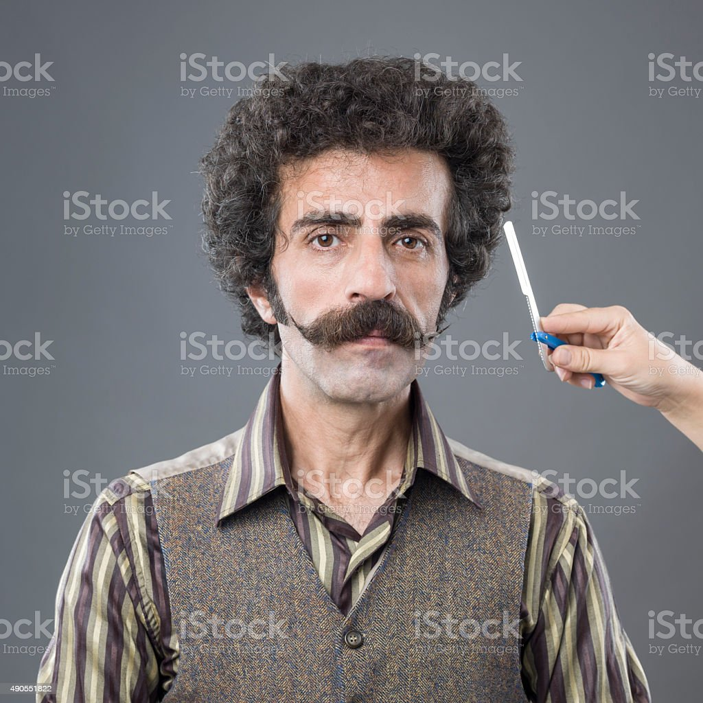Woman Hand Holding Razor Over Man's Handlebar Mustaches stock photo