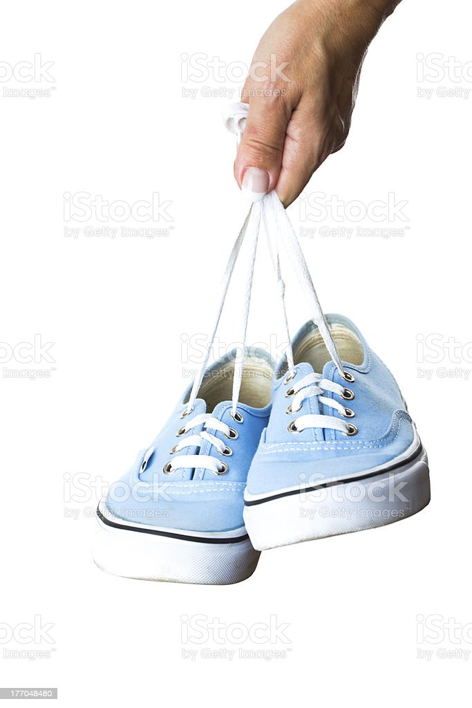 Woman hand holding sneakers on white background royalty-free stock photo