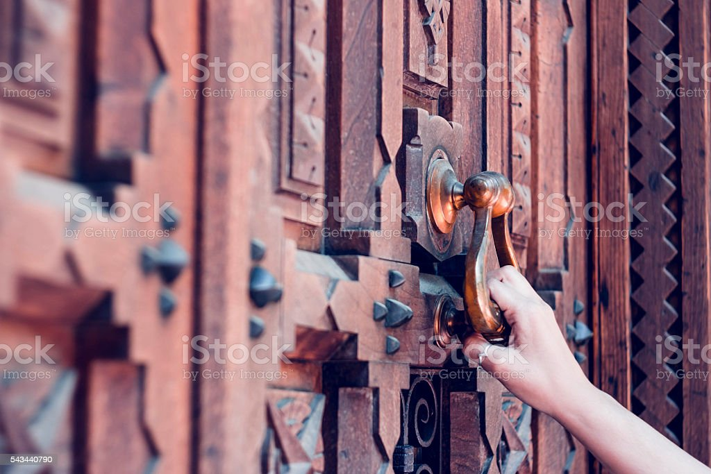 woman hand holding vintage old door, knocking stock photo