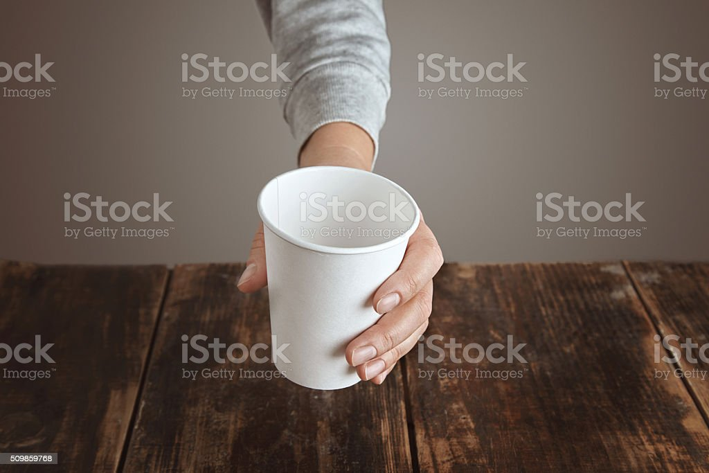 Woman hand holds paper glass above table stock photo
