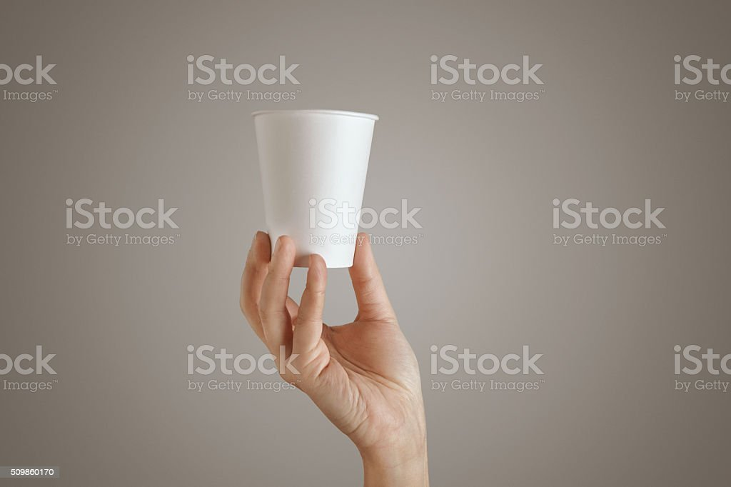 Woman hand holds paper glass bottom center isolated stock photo