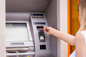 woman hand inserting credit card to ATM