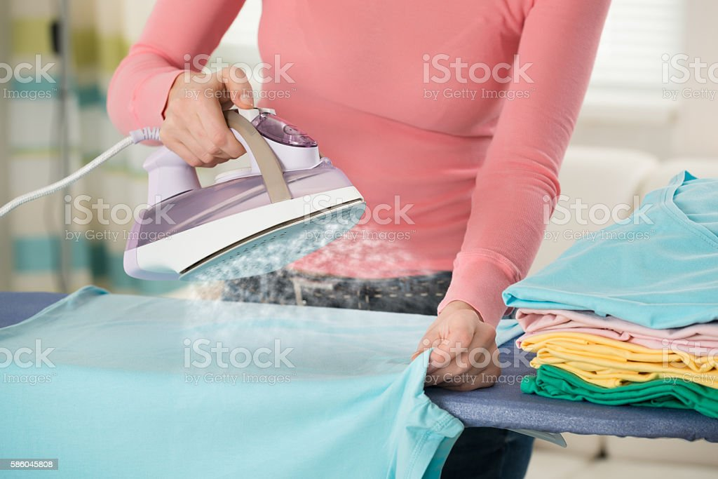Woman Hand Ironing Clothes stock photo