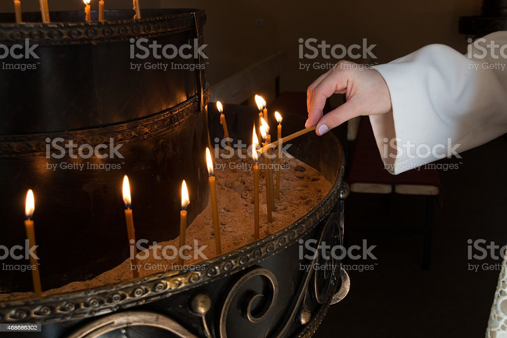 woman hand lighting candles in a church stock photo