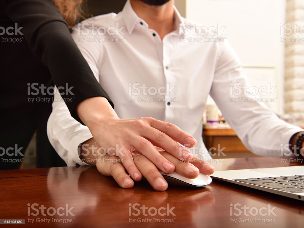 Woman hand on mans, working on laptop stock photo