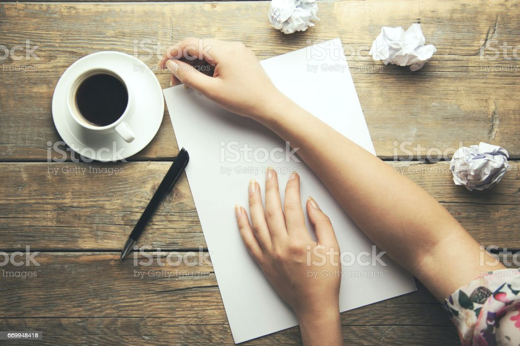 woman hand  on notebook and coffee cup and papers  on wooden table background stock photo