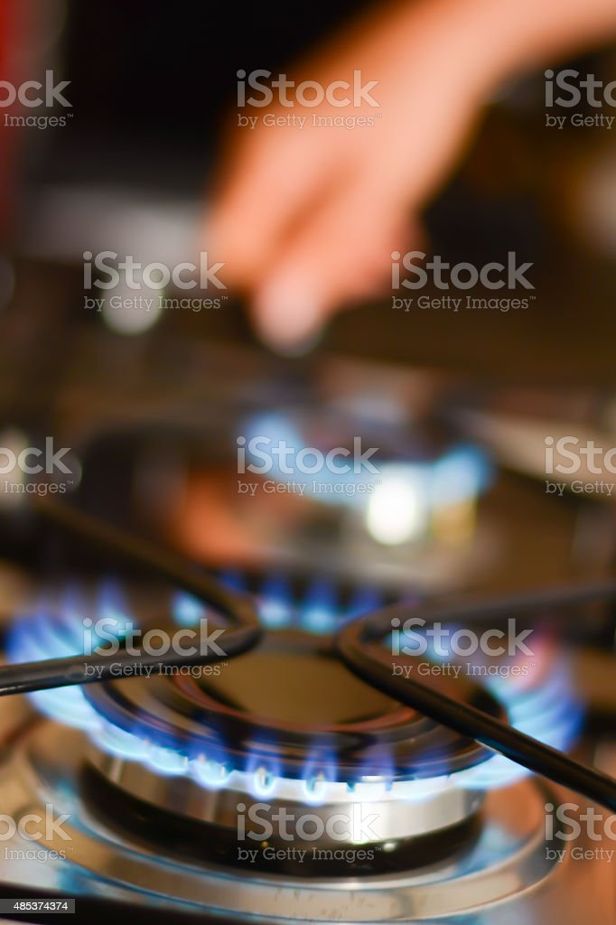 Woman hand opening a gas flame stove stock photo