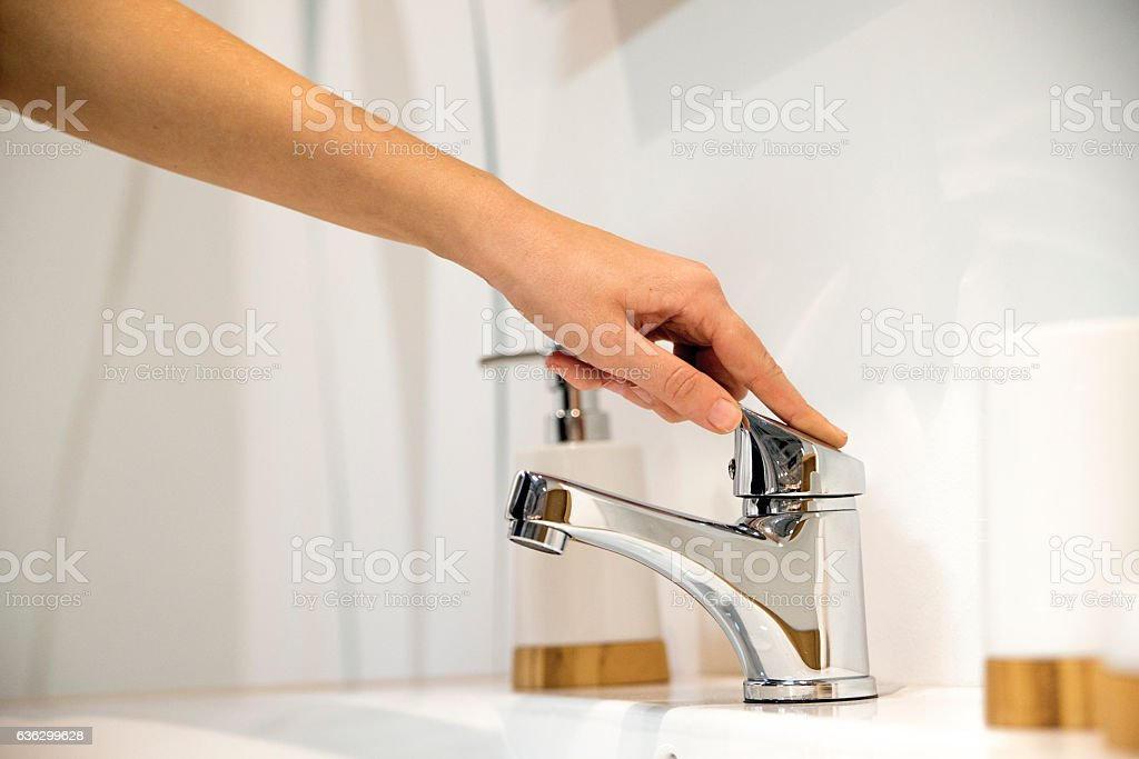 Woman Hand Operating Faucet stock photo