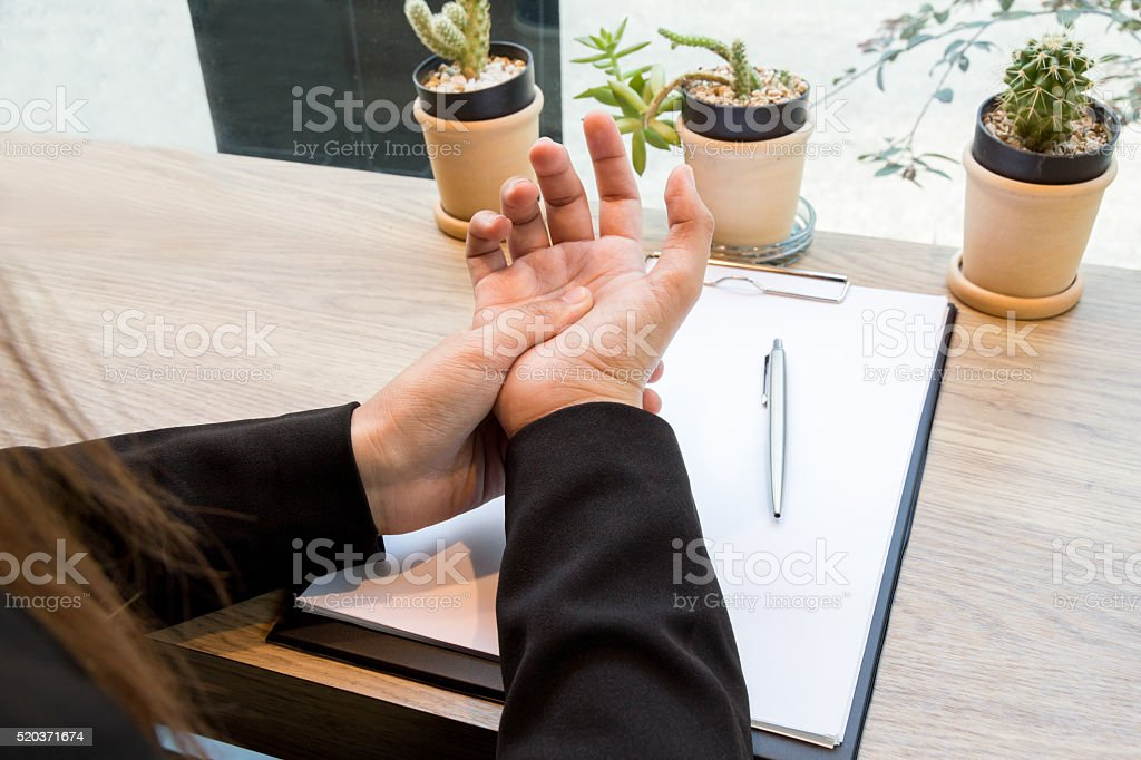 Woman hand pain on desk office syndrome stock photo