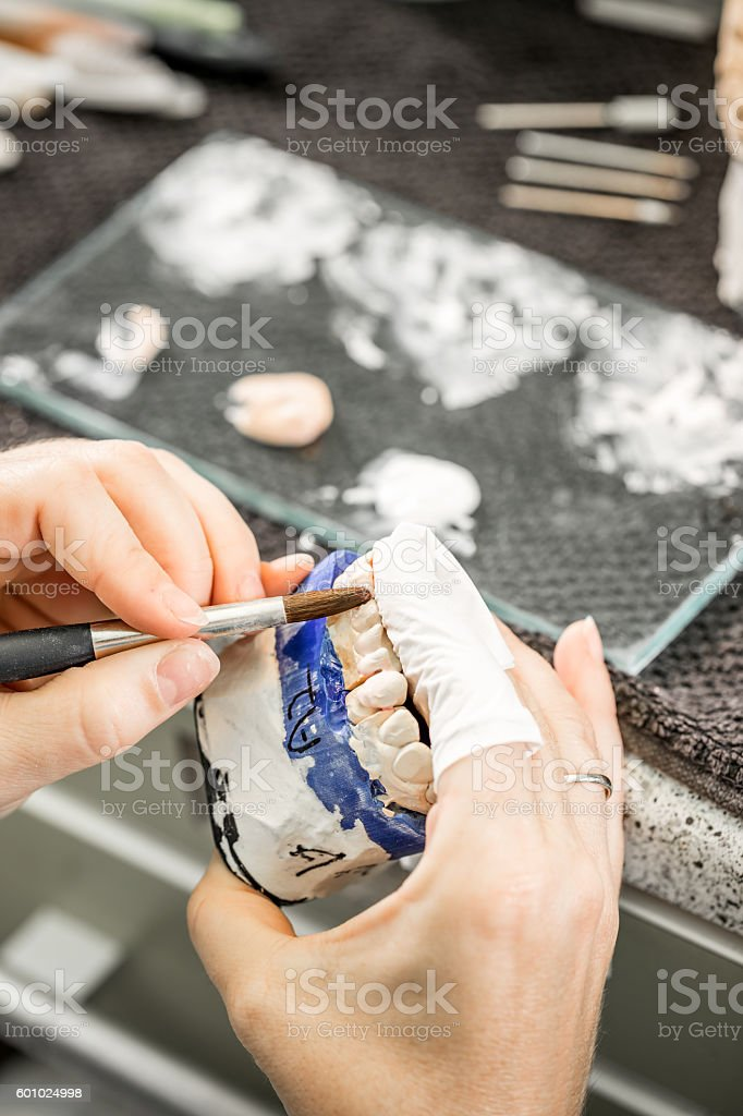 Woman hand painting denture stock photo