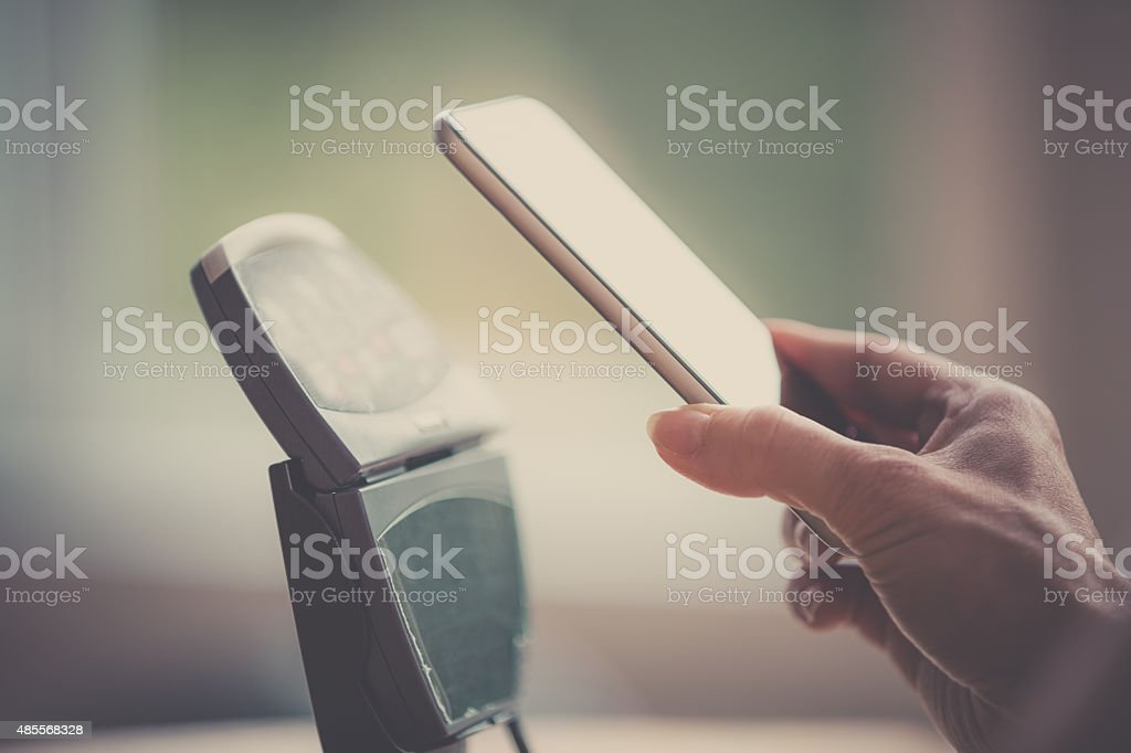 Woman Hand Paying using Smart Phone and Electronic Reader stock photo