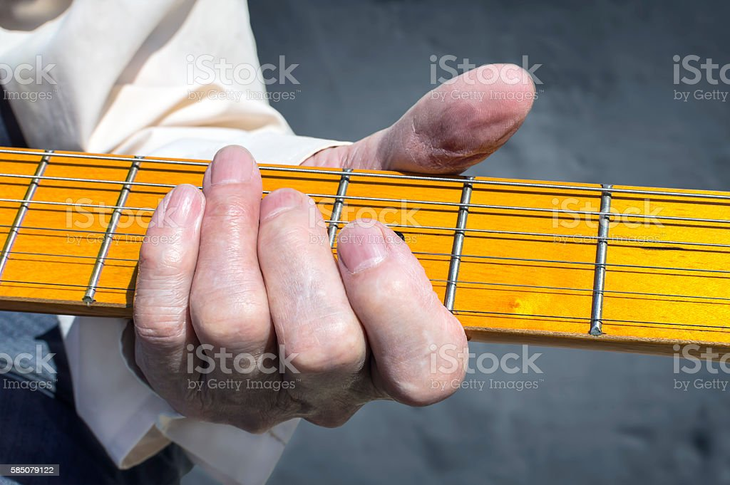 Woman hand playing electric guitar. stock photo
