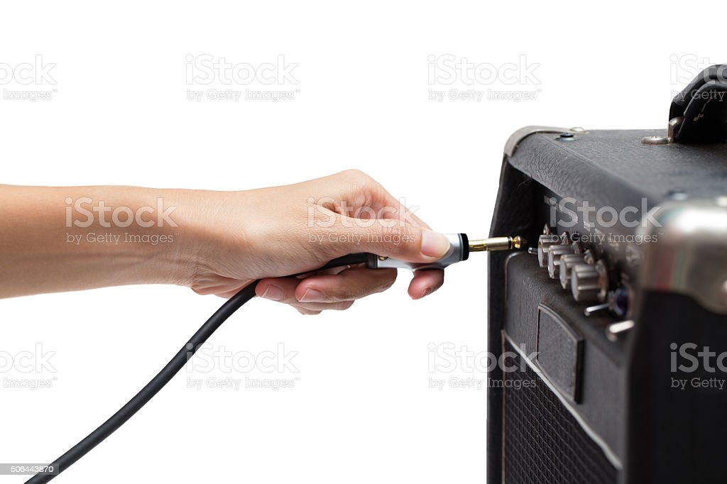 woman hand plugging into the amplifier guitar on white backgroun stock photo