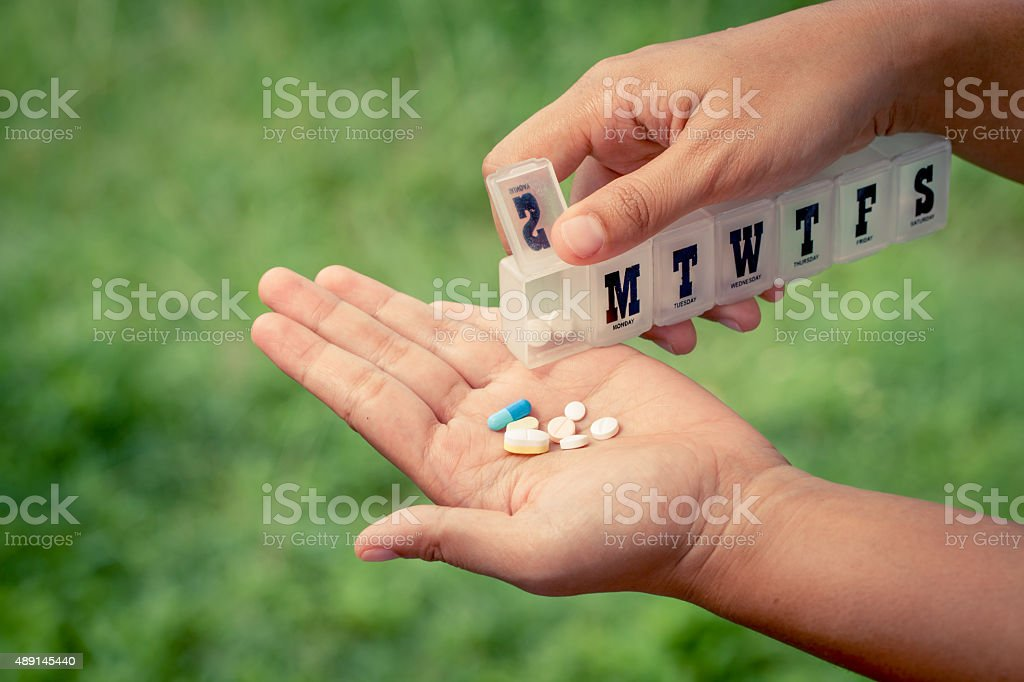 woman hand pouring pills from a pill reminder box stock photo