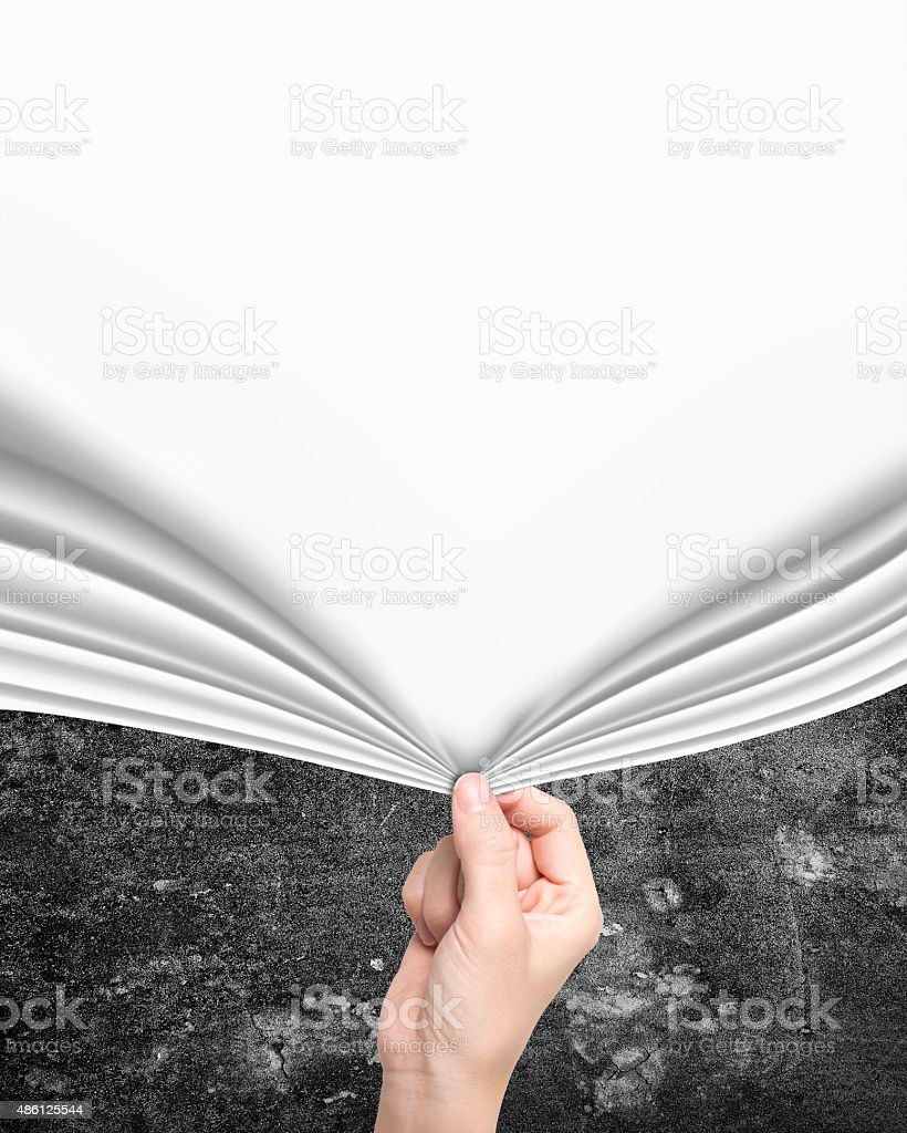 Woman hand pulling new white curtain covering old wall stock photo