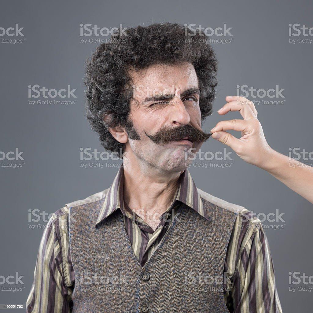 Woman Hand Pulling Up Adult Man's Handlebar Moustache stock photo