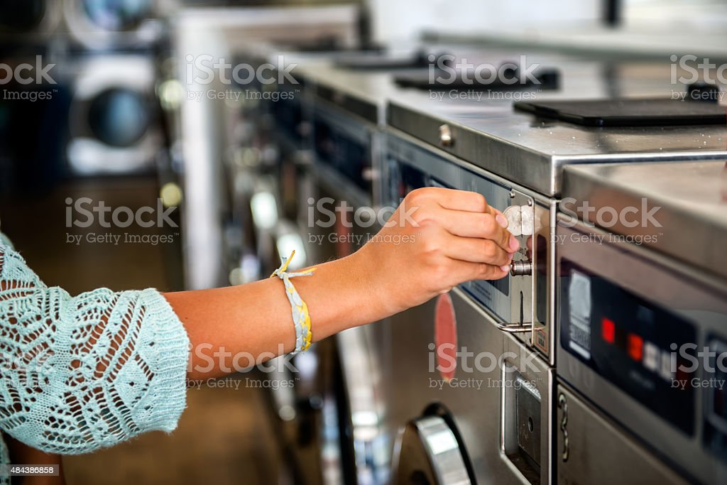 woman hand put quarter coin on laundry machine stock photo