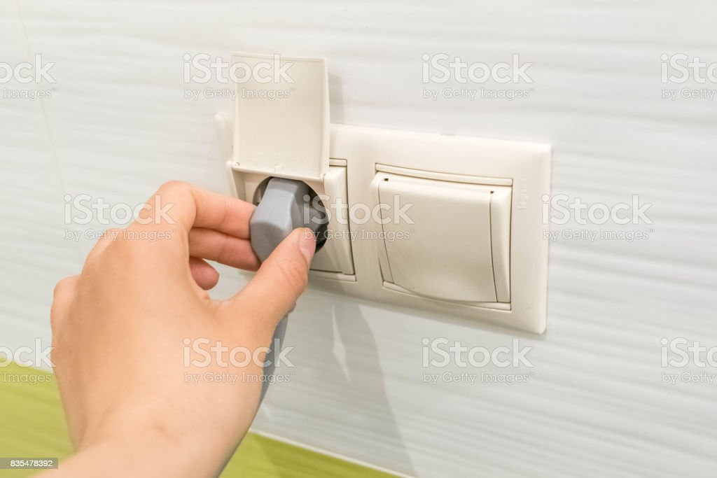woman hand puts plug in the socket, closeup shot. Hand Putting Plug Into Electricity Socket. Female hand unplugging a plug from a socket stock photo