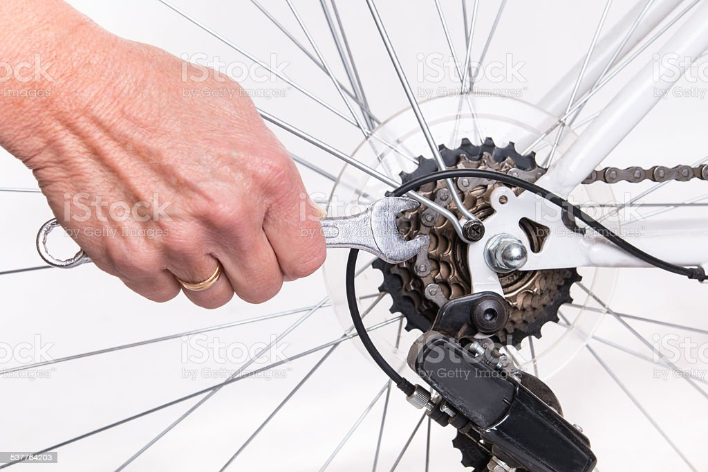 Woman hand repair bicycle whee with screw key stock photo