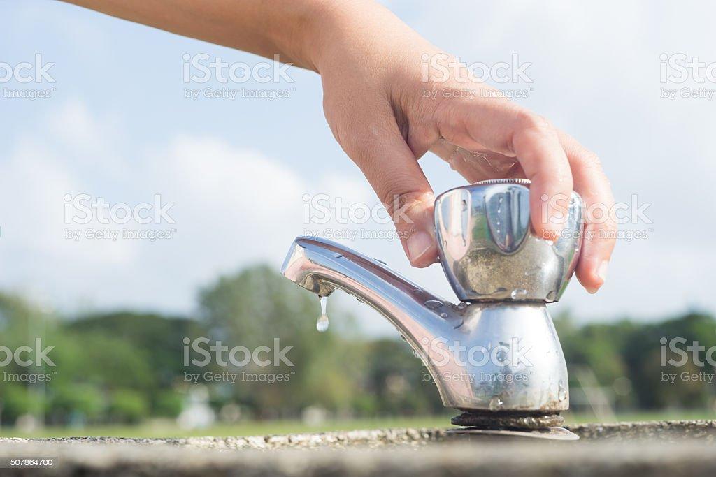 Woman hand shut the faucet. stock photo