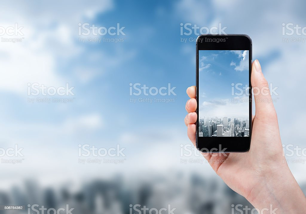woman hand taking photo of the city with a smartphone stock photo