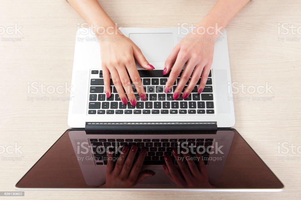 Woman hand typing on laptop keyboard stock photo