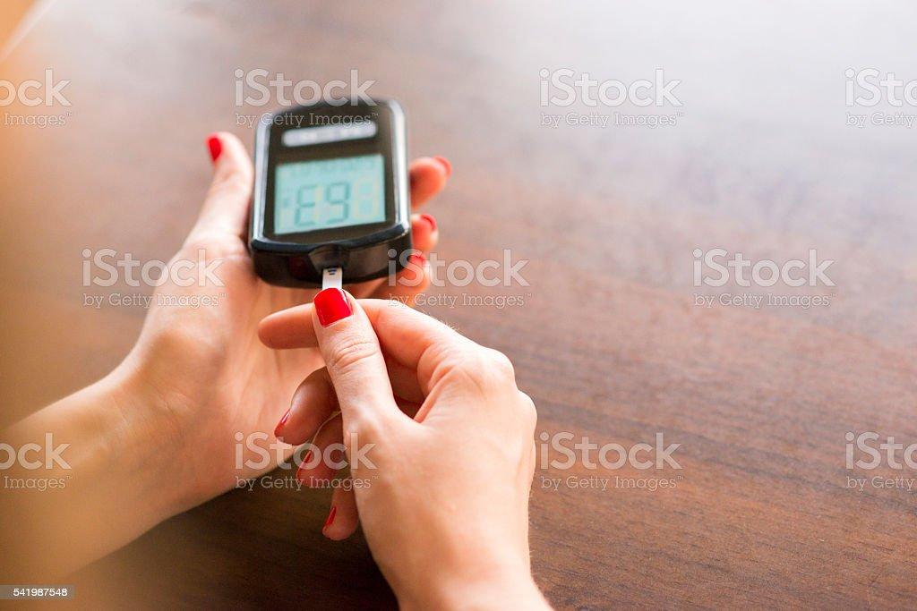 Woman Hand Using Glucometer To Check Blood Sugar Level stock photo
