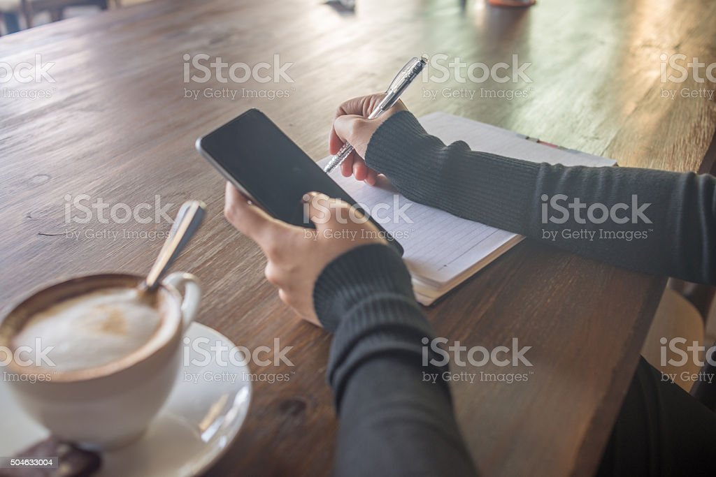 Woman hand using smartphone and taking note with Cappucino beside stock photo