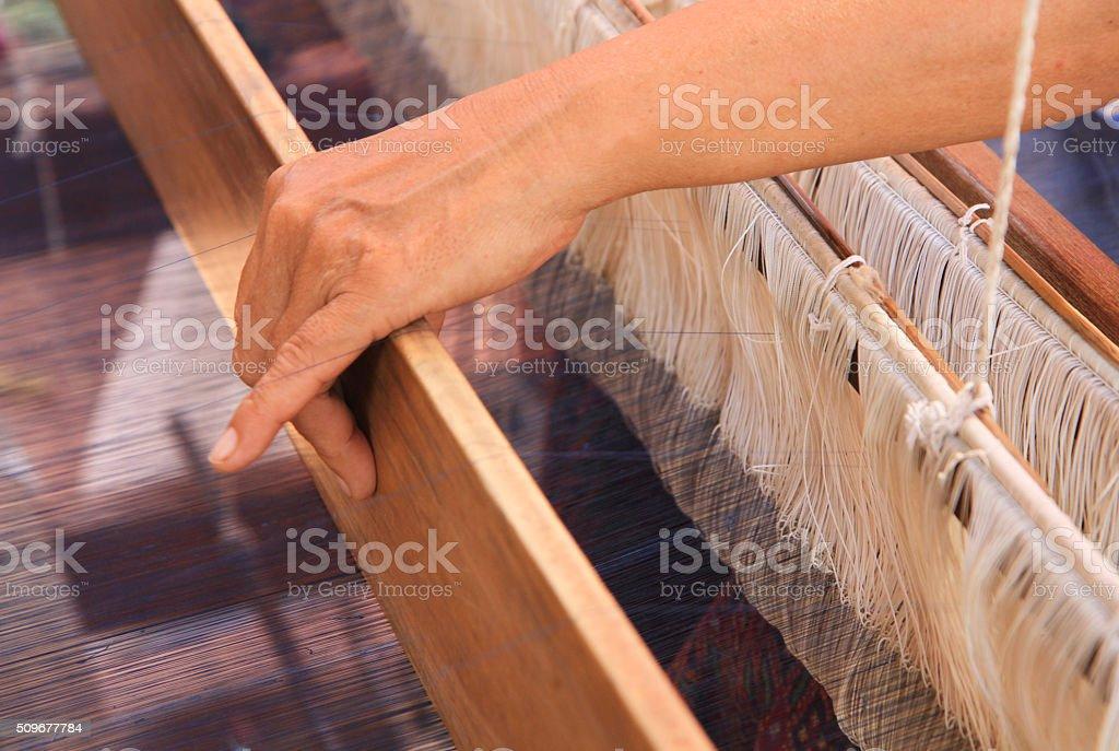 Woman hand weaving pattern on loom stock photo