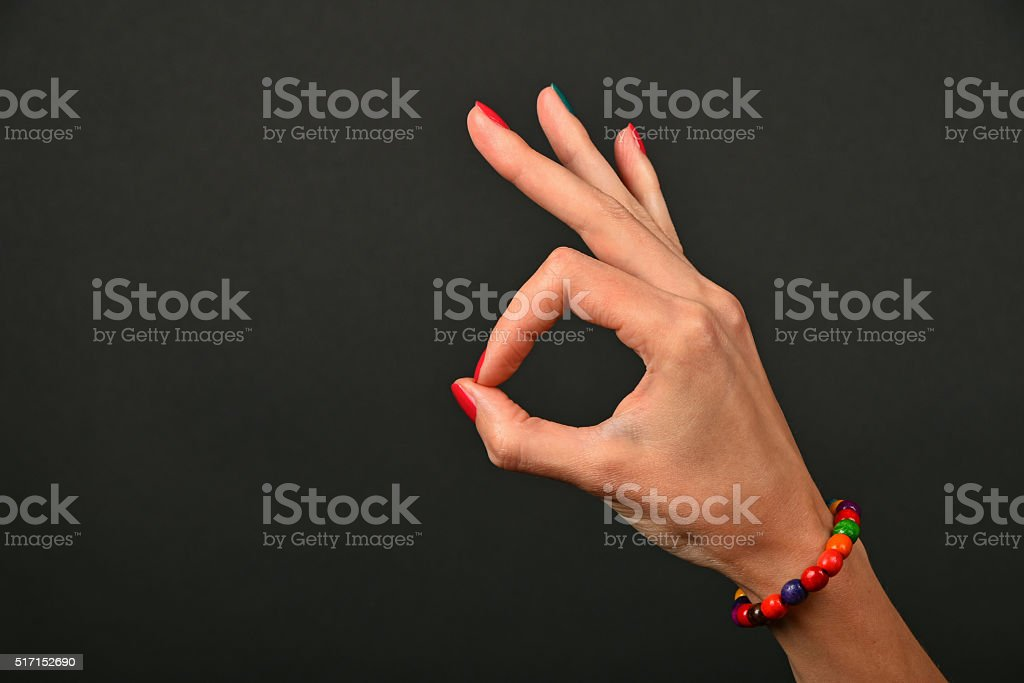Woman hand with beads shows ok gesture over black royalty-free stock photo