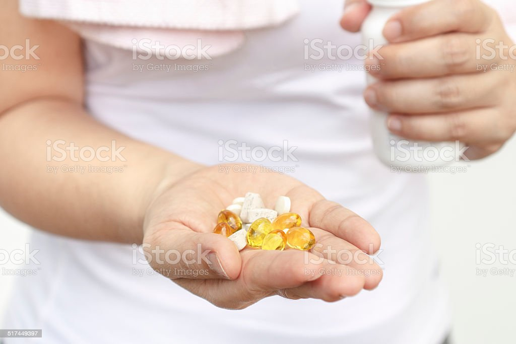 Woman hand with Cod liver oil and supplements stock photo