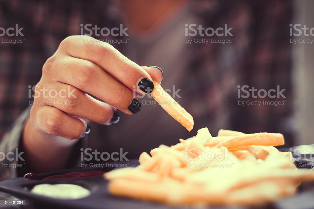 woman hand with green nails toasting french fries in restaurant stock photo