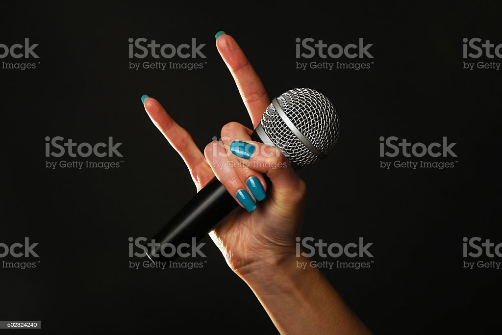 Woman hand with microphone and devil horns isolated on black royalty-free stock photo