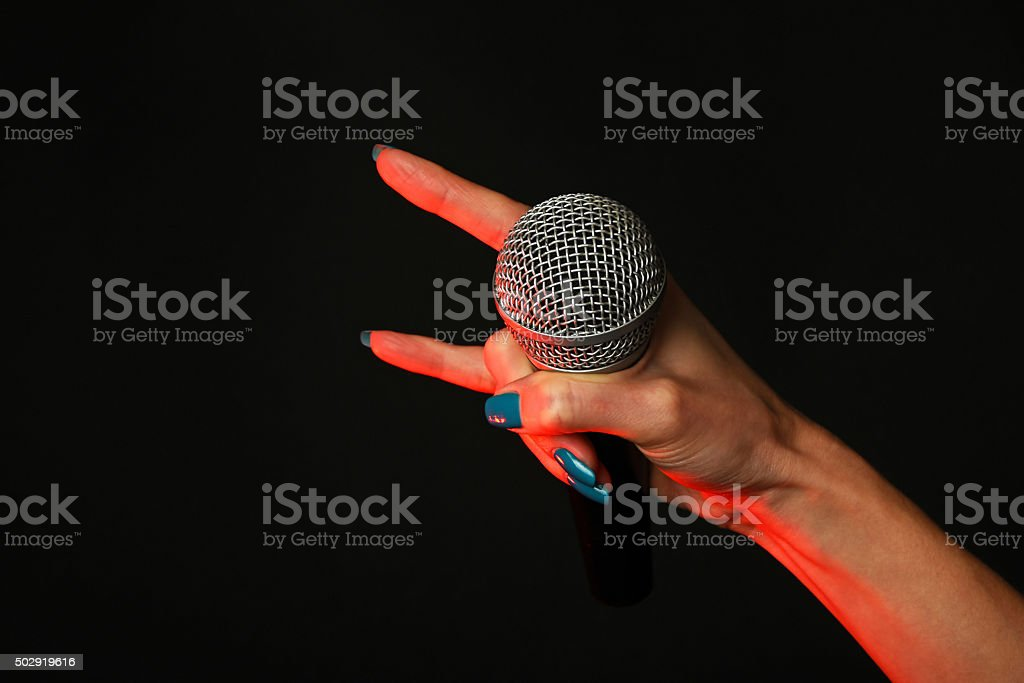 Woman hand with microphone and devil horns on black royalty-free stock photo