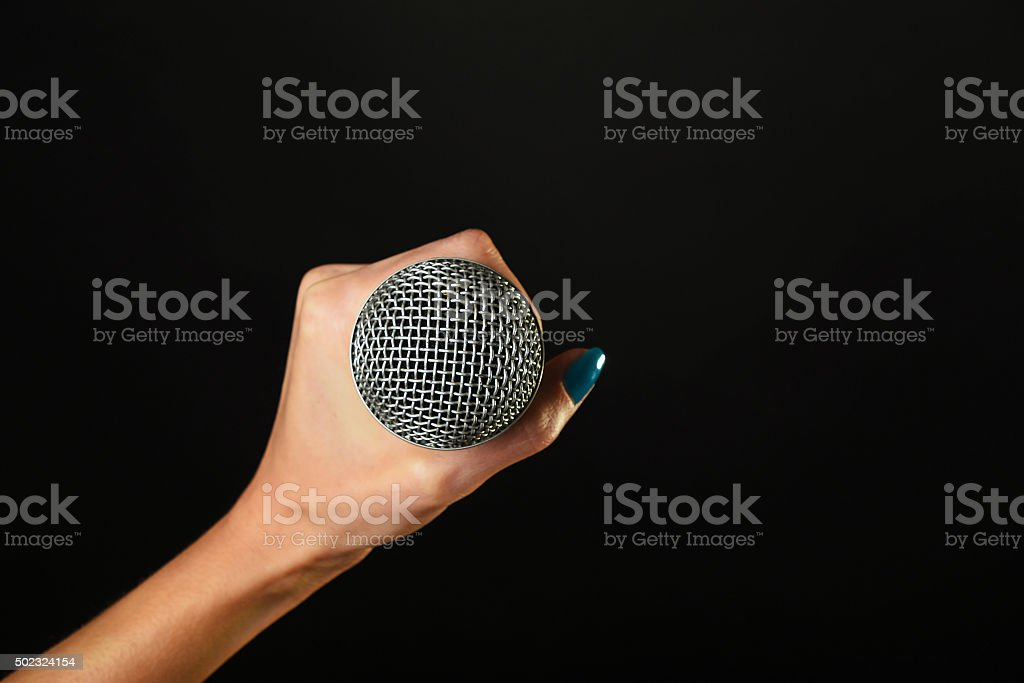 Woman hand with microphone isolated on black royalty-free stock photo
