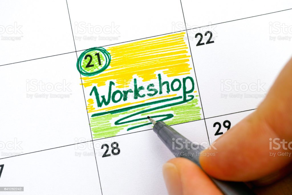 Woman hand with pen writing reminder Workshop in calendar stock photo