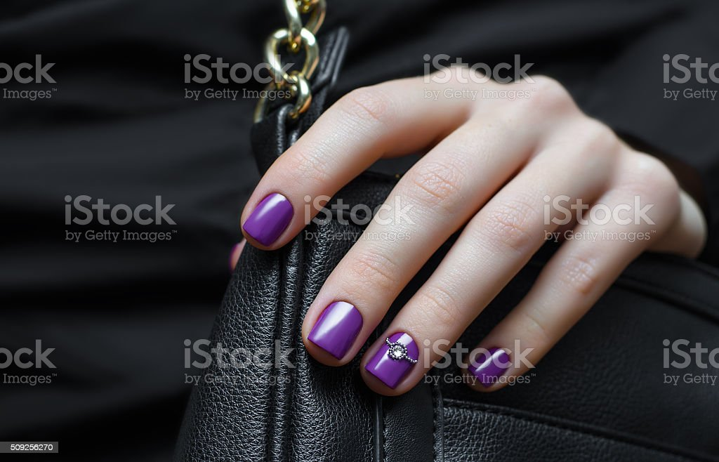 Woman hand with purple nail design. stock photo