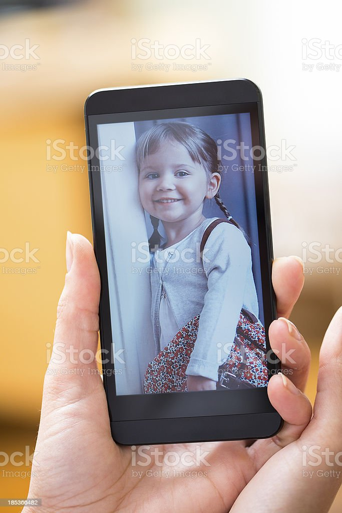 Woman hand with smartphone showing kid picture stock photo