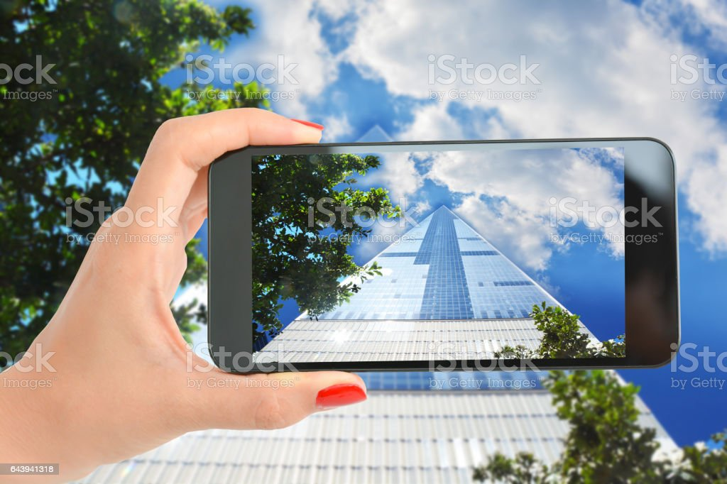 Woman hand with smartphone tacking a picture at One World Trade Center, Manhattan New York stock photo