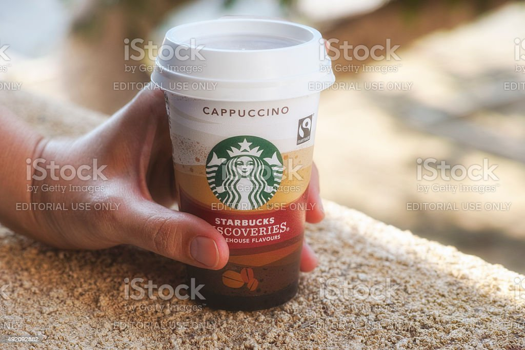Woman hand with Starbucks cup of cappuccino stock photo