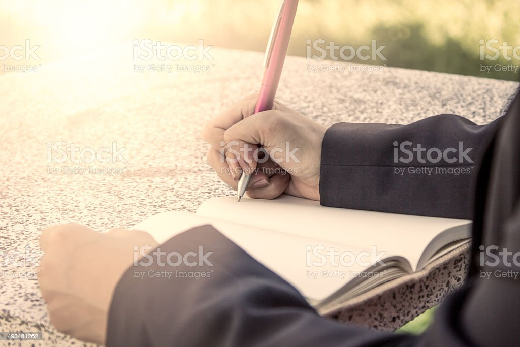 Woman hand writing her notebook,vintage filter stock photo
